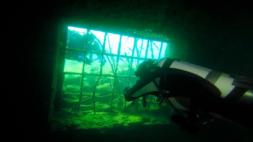 Filmowanie podwodne - dwóch nurków po dwóch stronach kraty w zatopionym budynku