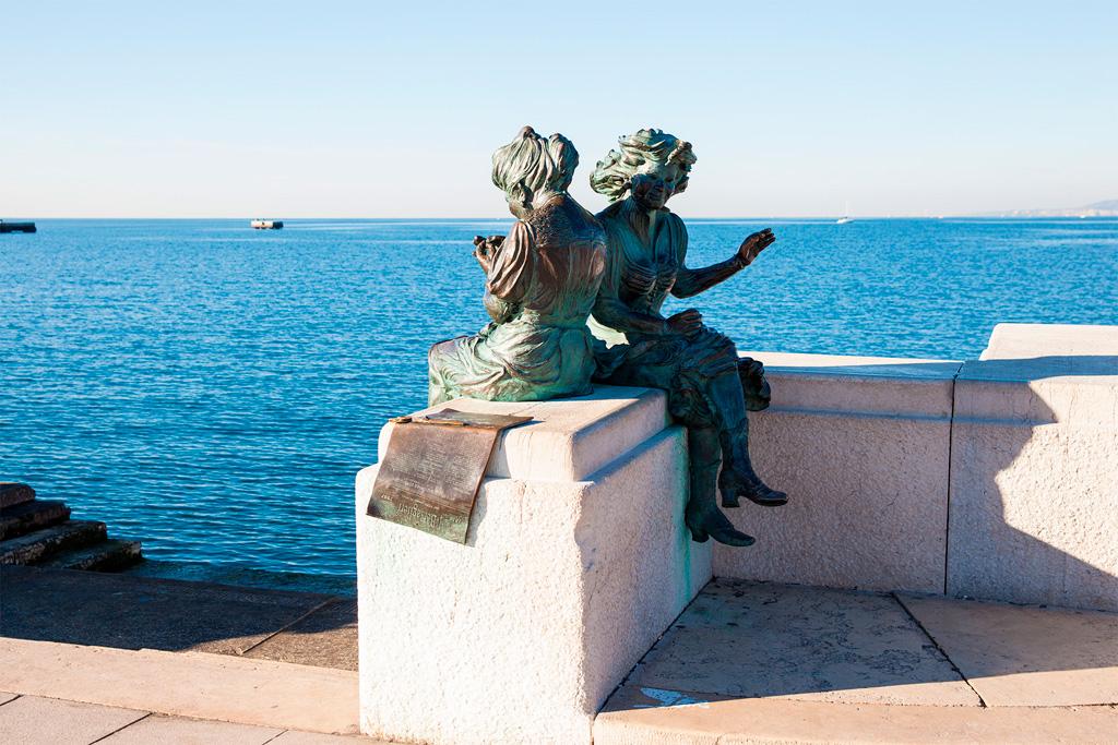 Pomnik - dwie panny siedzące na murku nad wodą