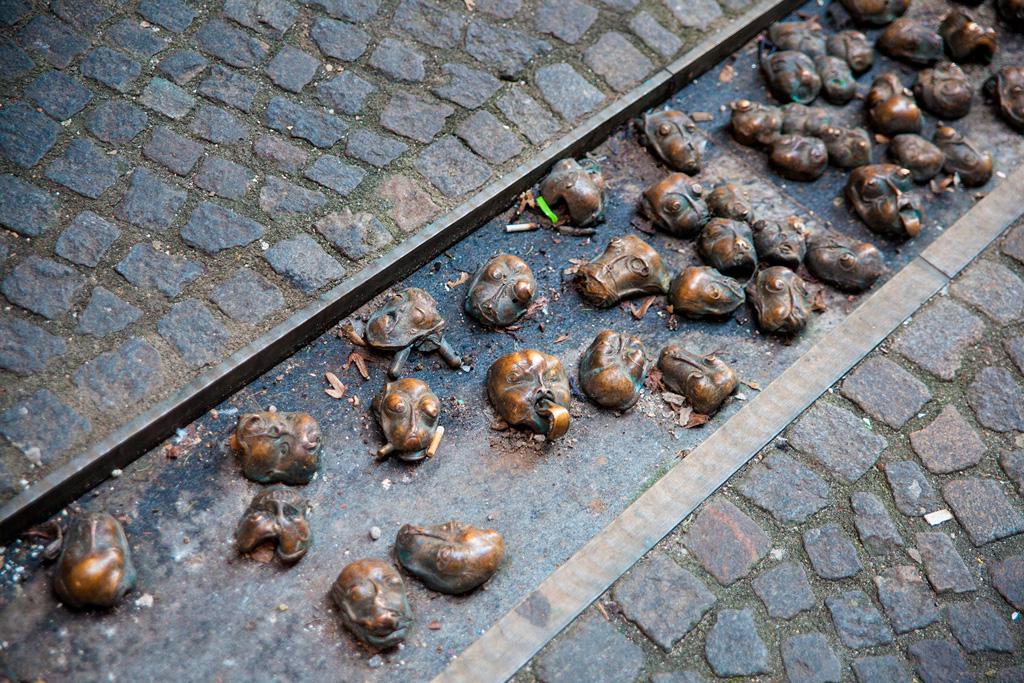 Nietypowa długa rzeźba uliczna - małe dziwaczne główki w rynsztoku