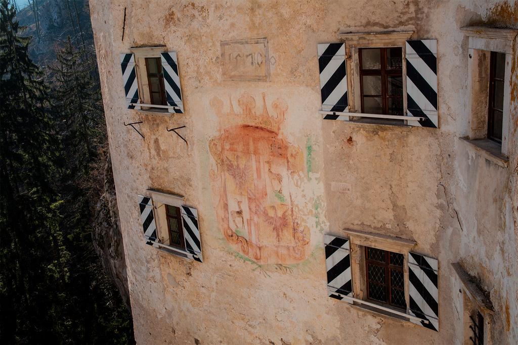 Zewnętrzne mury zamku z małymi oknami z okiennicami