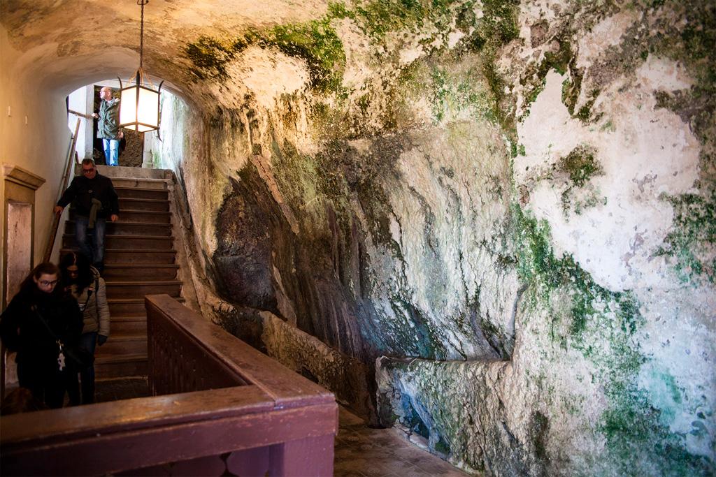 Po lewej stronie schodów ściany zamku, po prawej skała jaskini.