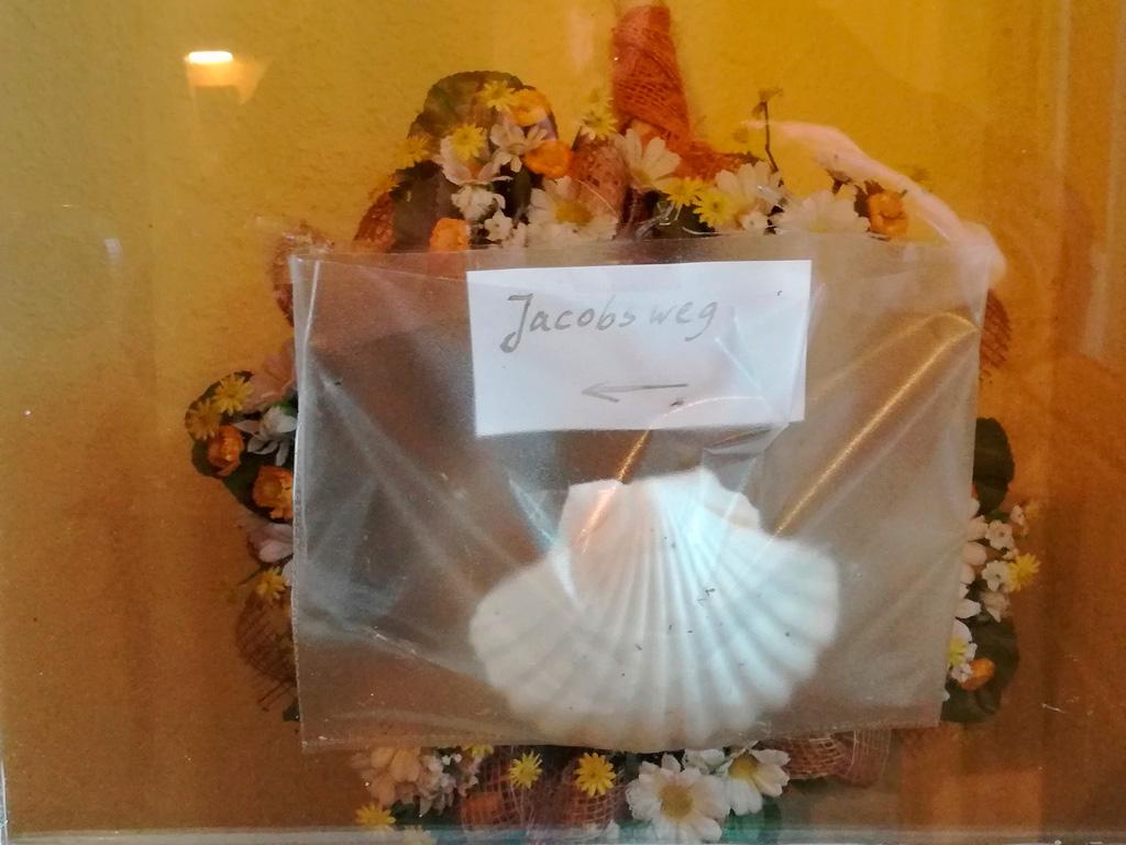 Nietypowe oznaczenie Camino - muszla na drzwiach kawiarni na Uznam