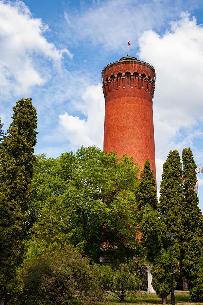 Filtry Warszawskie - wysoka ceglana wieża wśród drzew