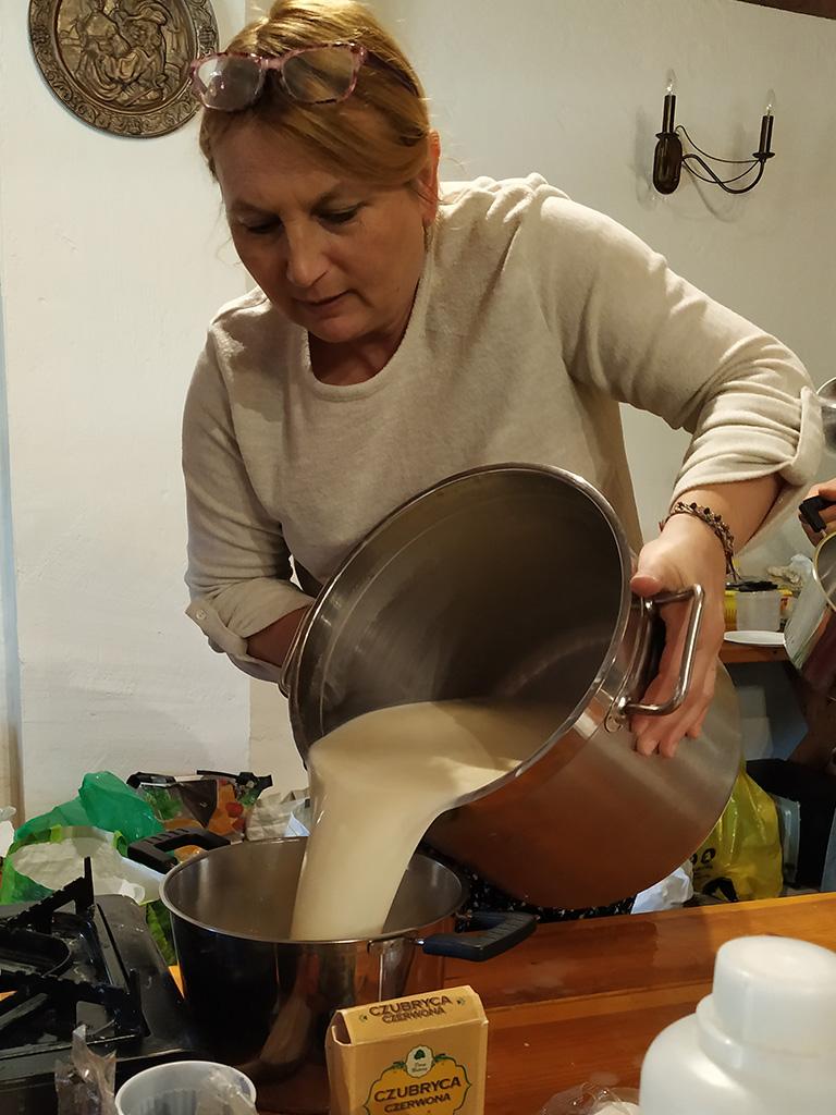 Warsztaty serowarskie w trakcie – przelewanie mleka