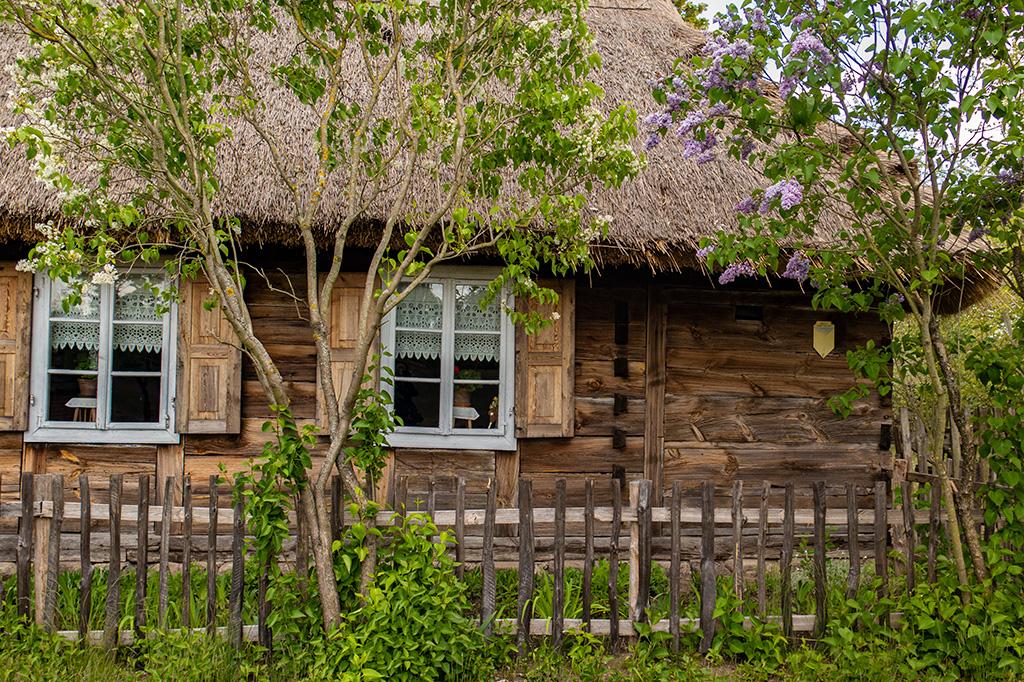 W skansenie w Maurzycach chaty otoczone sądrewnianymi płotkami
