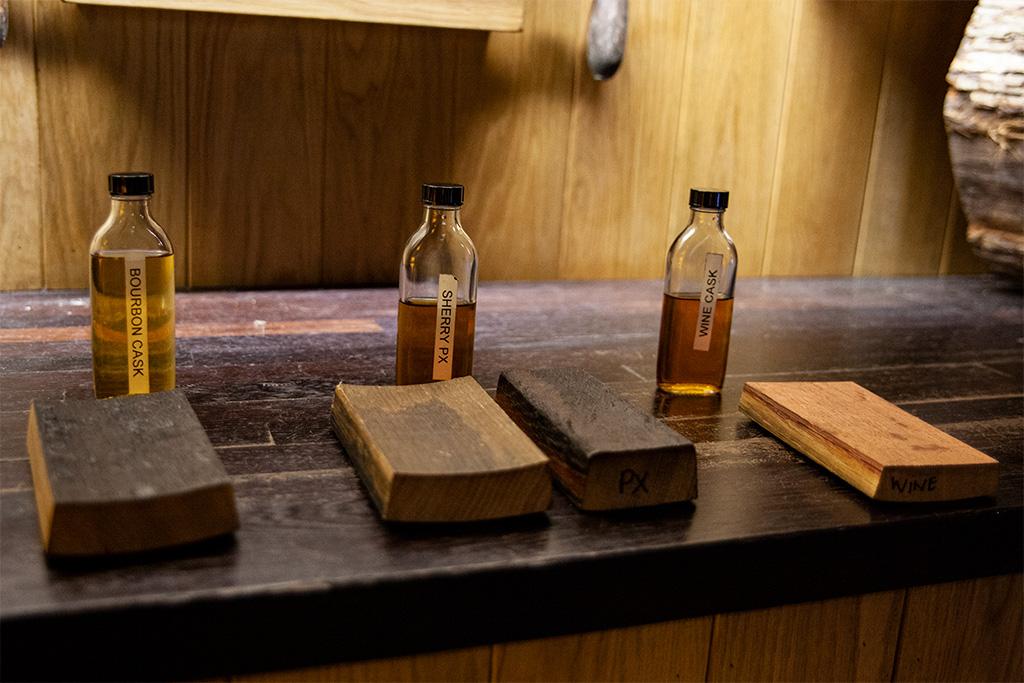 Fragmenty beczek i whisky w nich leżakująca. Ta z beczki po bourbonie jest zdecydowanie jaśniejsza.