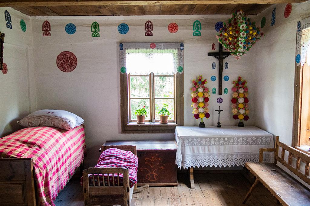Wnętrze chaty ozdobione wycinankami i pająkiem